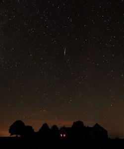 En klar perside lyser op på stjernehimlen over gården.